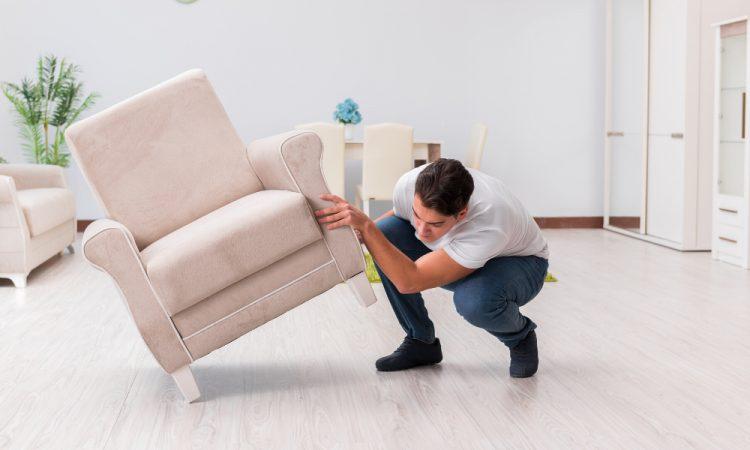 man checking hardwood under chair