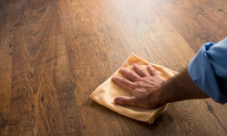 man scrubbing hardwood with tack cloth