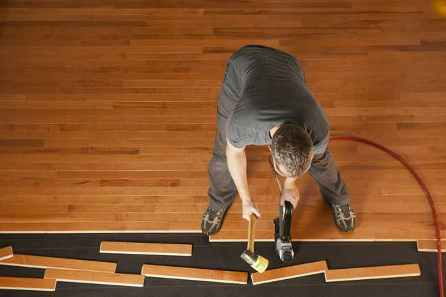 Hardwood Flooring professional installing tongue and groove flooring