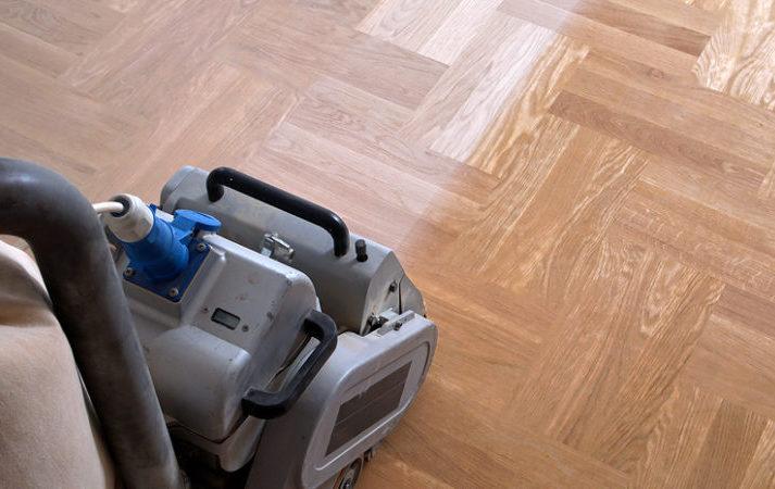 Sanding hardwood floor with the grinding machine. Repair in the apartment. Carpenter doing parquet wood floor polishing maintenance work by grinding machine