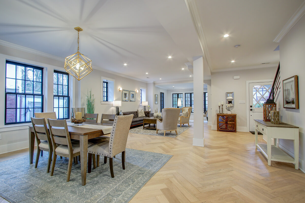 A living room with hardwood floors, tables, chairs and couches