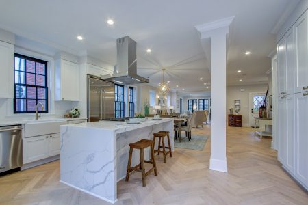 A living room and kitchen with St. Paul's Herringbone engineered floors