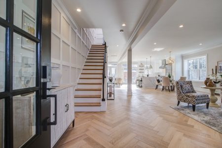 Inside of a house in front of the steps with hardwood floors