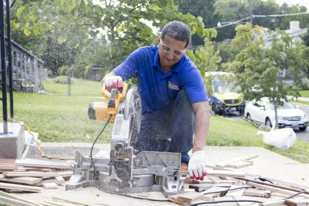 A man outside working with flooring tools to fix a residential floor